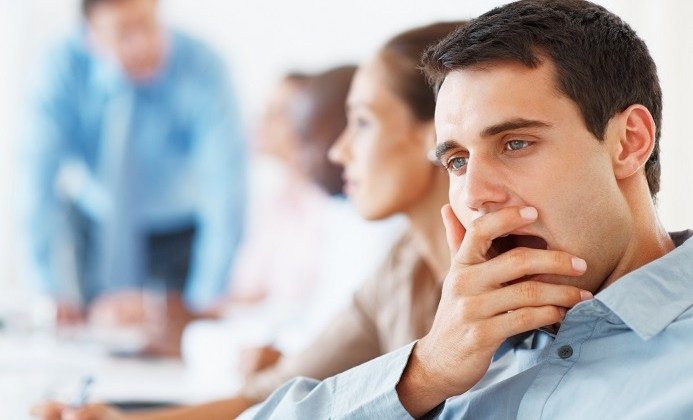 Closeup of young business man yawning during meeting with colleagues in background