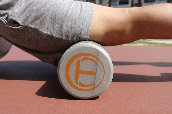 Using a foam roller to massage your muscles is a good active recovery workout idea.